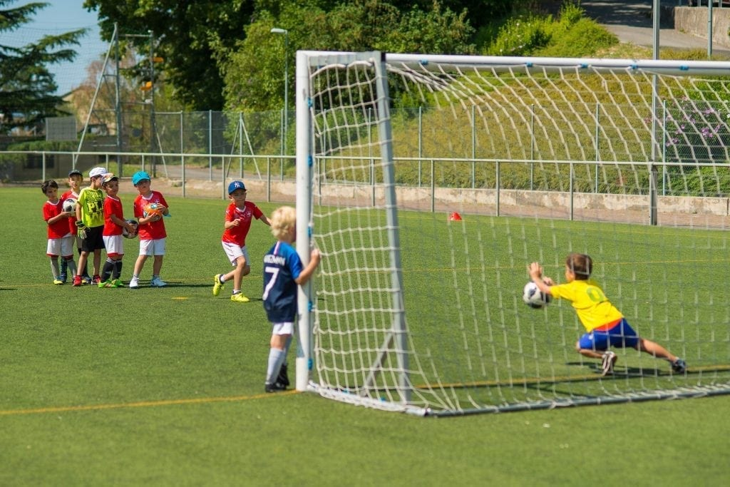 Children in Basel are lining up to take a shot at the goal with a very enthusiastic goalkeeper trying to stop the football